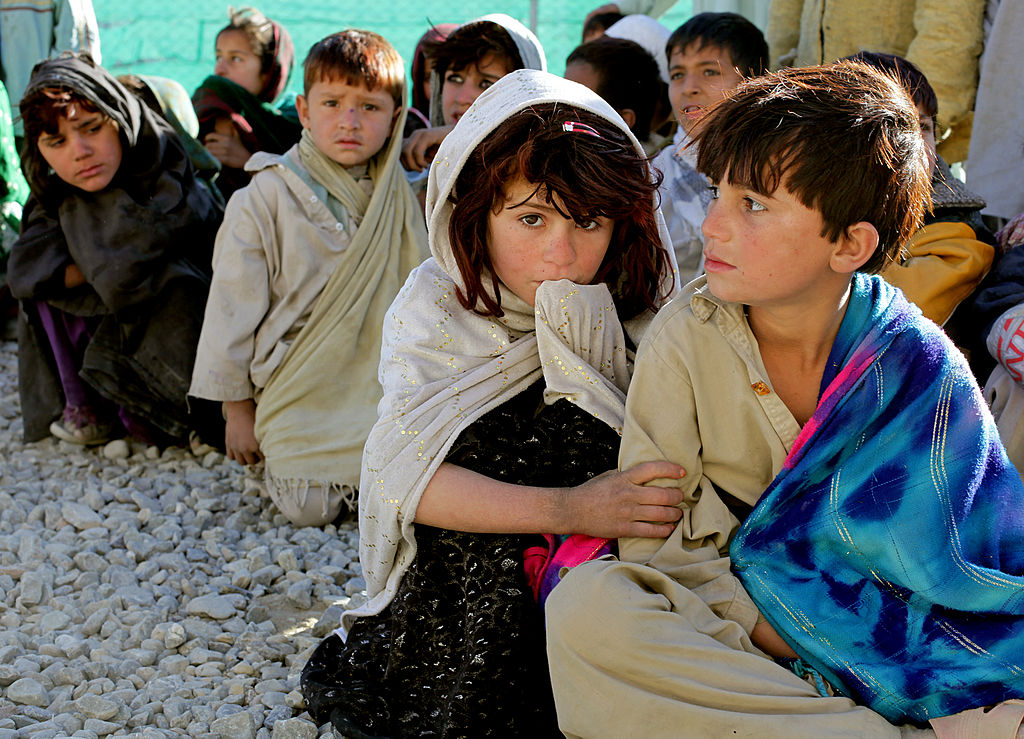 Afghan children wait to receive basic medical care and clothing on Camp Clark