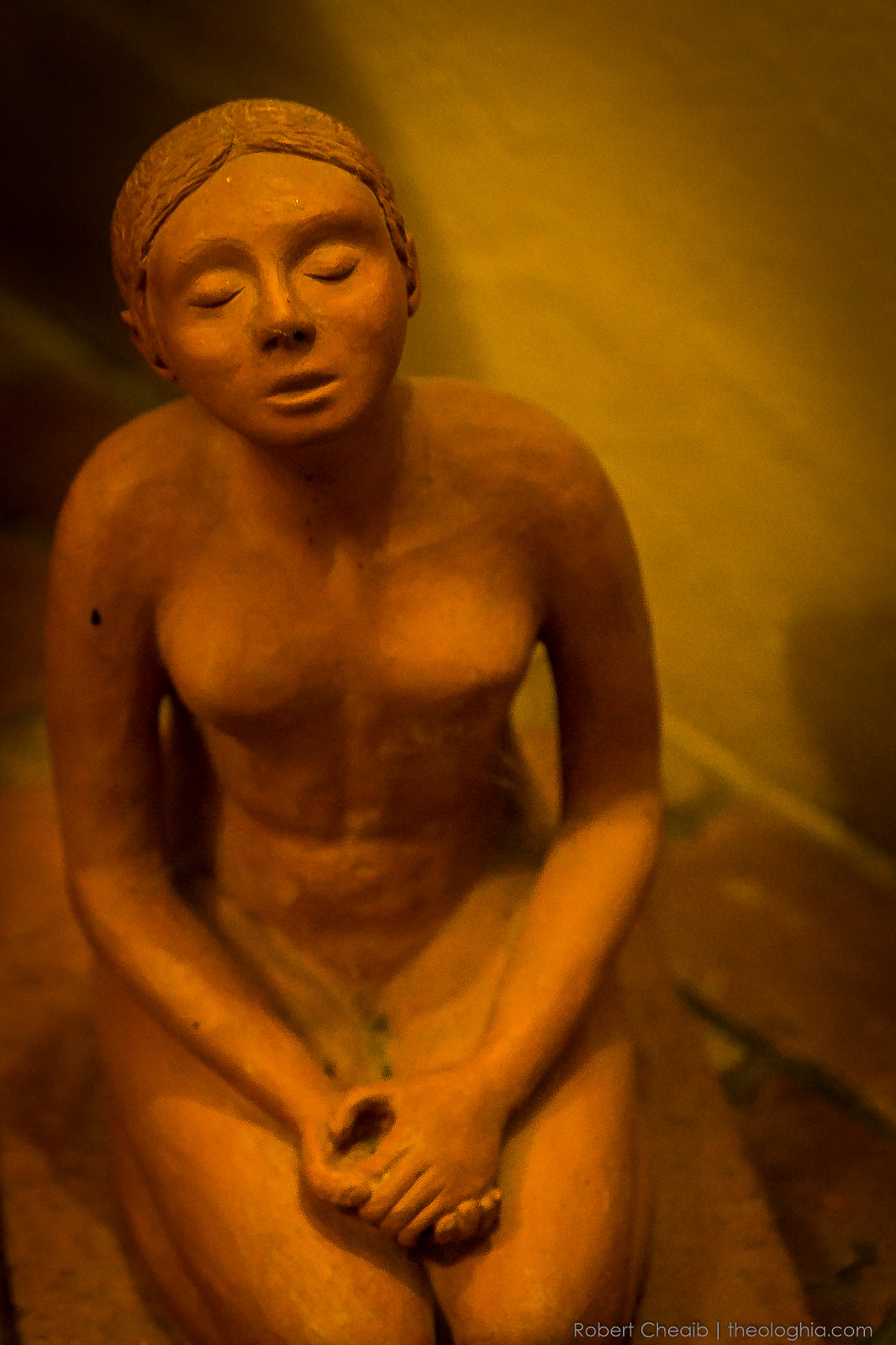 Clay statue of a woman in prayer and meditation
