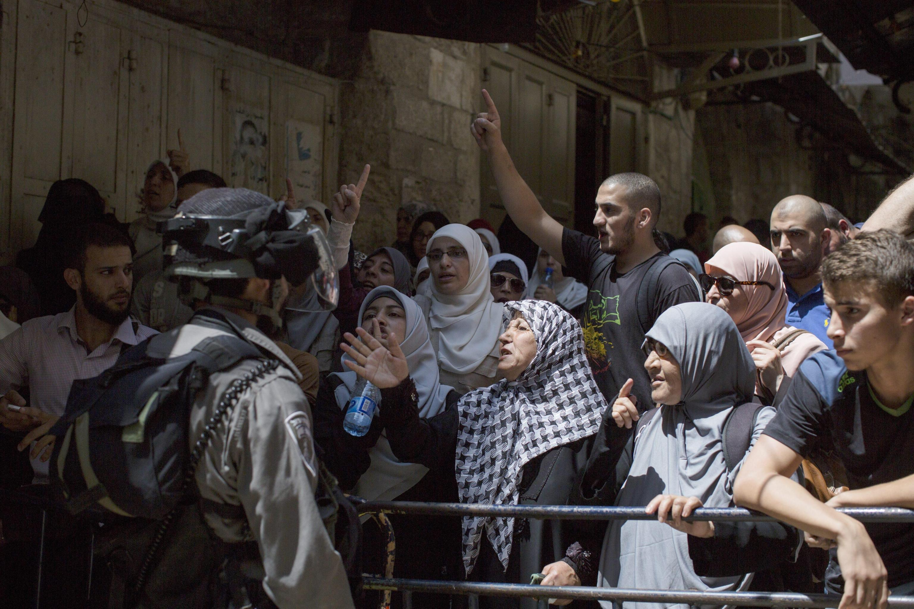 Israeli border police block Palestinians from entering into the Al-Aqsa mosque compound in the Old city of Jerusalem
