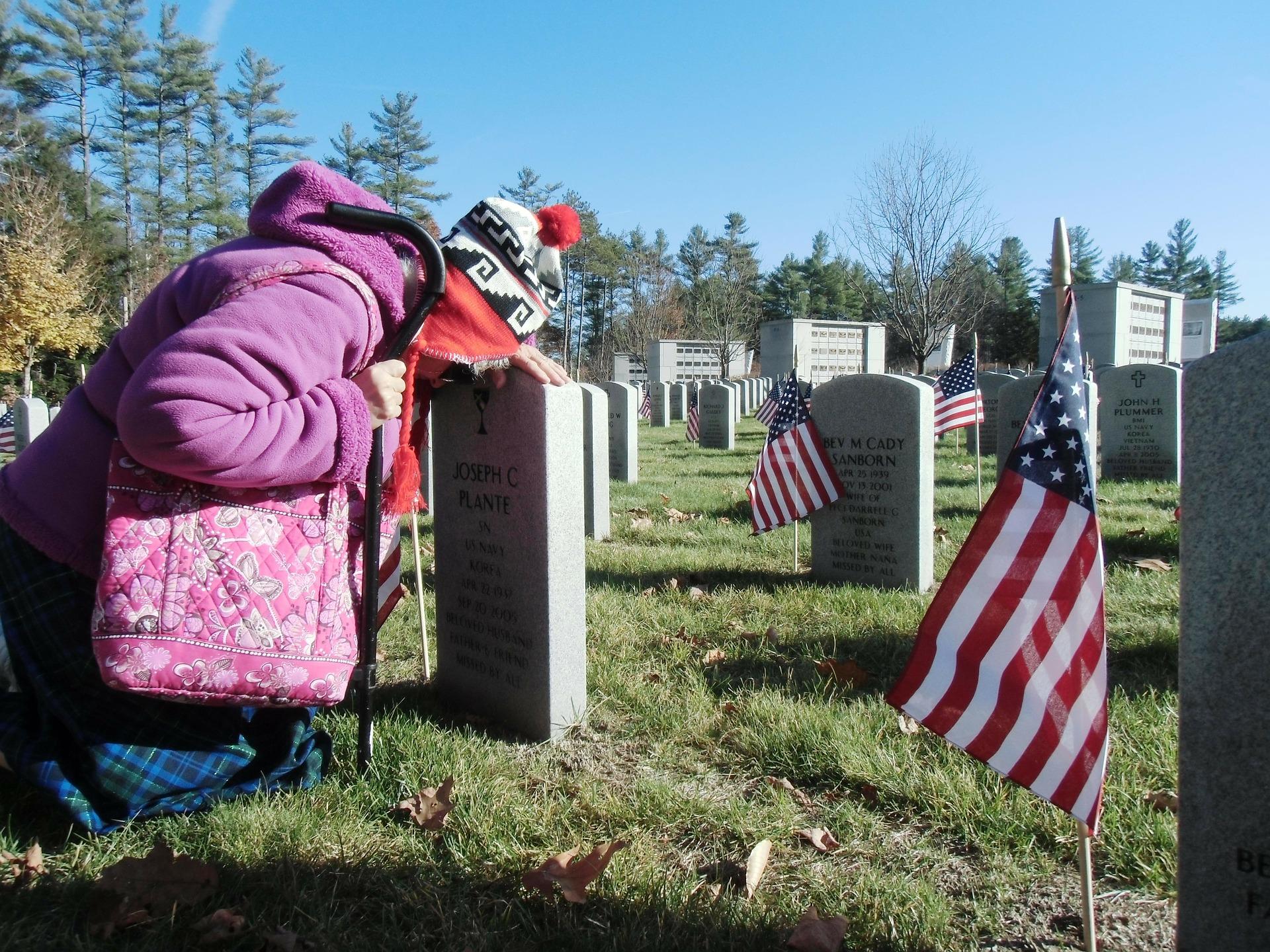 A widow seeking comfort prays at the tomb of her husband