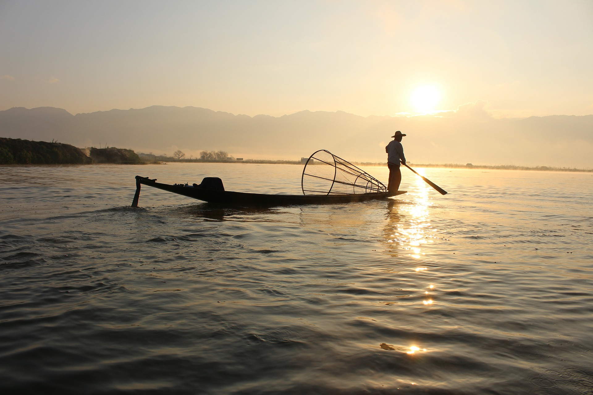 A fisherman in his boat on the Lake Inle