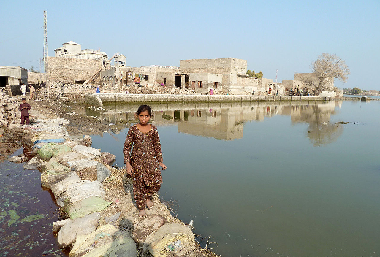 A young girl walks across a makeshift bridge over stagnant flood-water in Sindh province